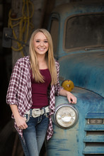 Beautiful Young Lady Standing Next To An Old Blue Truck