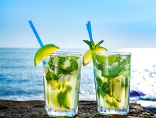 Cocktail Mojito With Ice And Lemon In Two Glasses On The Background Of The Ocean Closeup