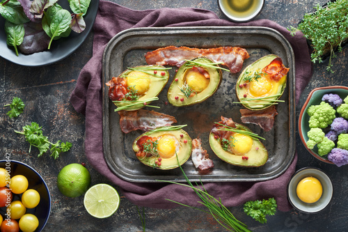 Recess Fitting Appetizer Baked avocado with egg and bacon on a metal baking tray, flat lay with ingredients and herbs on dark