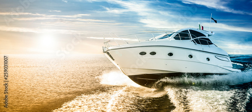 Fotografia  Luxurious motor boat sailing the sea at dawn