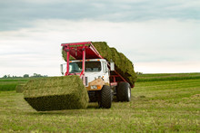 Picking Hay Bales In Field