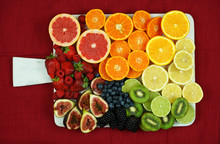 Colorful Fruit Platter Assembly With Rainbow Color Fruit Including Citrus, Berries, Figs, And Kiwi Fruit On White Marble Board Against Red Tablecloth.