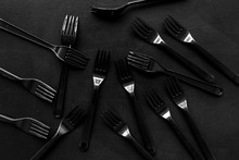 Plastic Flatware, Forks, Spoons, Knifes For Eco And Earth Protection Concept On Black Background Top View Pattern