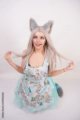 Fotomural funny girl with fluffy fur cat ears stands in kitchen apron on her knees and sho