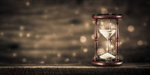 Vintage Hourglass On Wooden Table With Bokeh Background And Sepia Effect - Time Concept