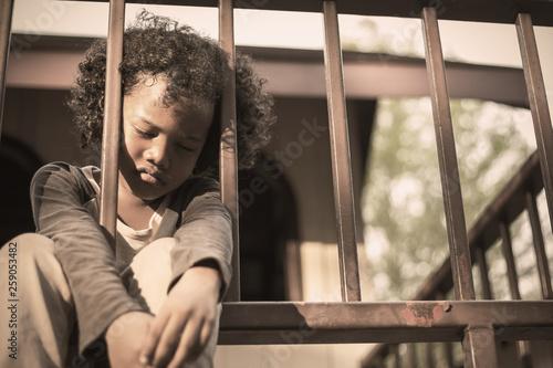 Fotografia Little boy sitting behind the fence