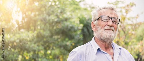 Fototapeta Portrait of stressful sad senior caucasian old man in the park outdoors with copy space. Spring healthcare lifestyle stress painful retirement golden age crisis concept banner obraz