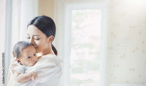 Foto  Close up portrait of beautiful young asian mother kissing her newborn baby