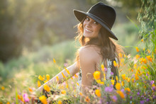 Beautiful Young Latino Woman In A Hat Smiling While Sitting Back To Camera In Poppy Fields At Sunset