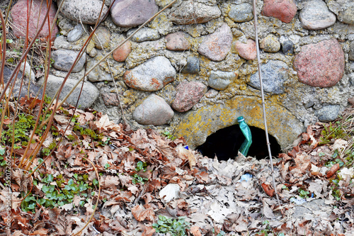 Fényképezés  Culvert pipe hole for draining sewage water covered with dry autumn leaves and polluted with plastic bottle