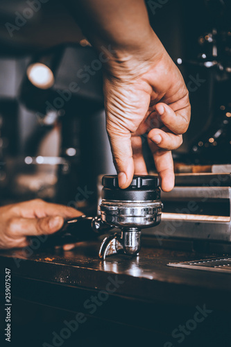 Professional Barista pressing tamping freshly ground coffee beans in a portafilter in coffee shop or cafe Wallpaper Mural