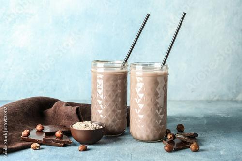 Carta da parati Glasses of protein shake on color background