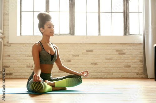 Sporty African-American woman practicing yoga indoors