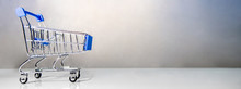 Miniature Blue Shopping Cart Or Shopping Trolley On The Table. Supermarket Grocery Push Cart. Banner For Buying Concept.