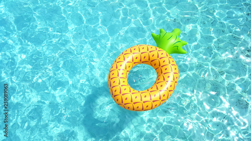 Fotografía Pineapple life ring floating in crystal blue sea water on a sunny day for relaxation and happy summer holiday vacations concept