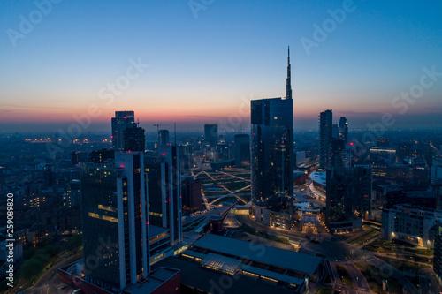 Fototapeta premium Mediolan (Włochy) panoramę miasta o świcie, widok z lotu ptaka, przelatujące nad wieżowcami obszaru finansowego w dzielnicy Porta Nuova. Budynek biurowy Unicredit Tower o wschodzie słońca.