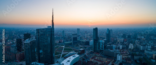 Fotografie, Obraz Milan (Italy) city skyline at dawn, aerial view, flying over financial area skyscrapers in Porta Nuova district