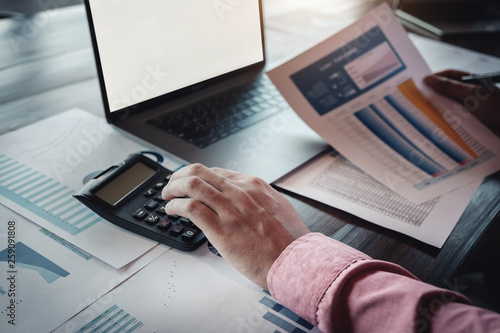 Bookkeeper accounting Concepts, Male use calculator, pen , and computer laptop to working financial and budget, inspector accountant concept.
