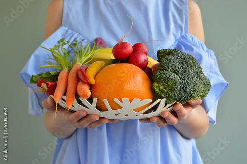 Fototapeta Crop shot of girl holding bowl with vegetables and fruits obraz