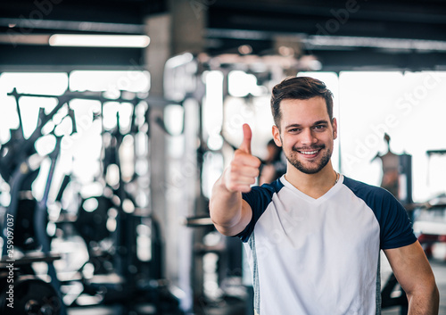 Smiling sportsman showing thumbs-up at the gym. Fotobehang