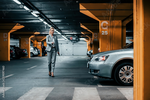 Leinwand Poster Successful businesswoman walking to her car in underground car parking