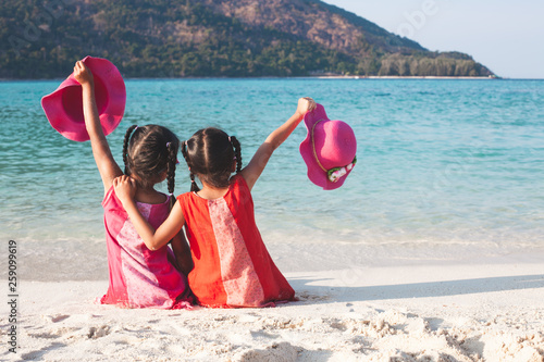 Leinwand Poster Two cute asian little child girls holding the hat sitting and playing together o