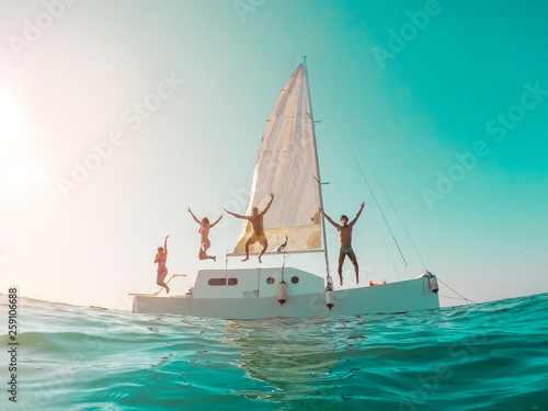 Fotografie, Obraz  Happy crazy friends diving from sailing boat into the sea - Young people jumping