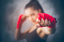 Image Focus The Fist Of The Beautiful Young Asian Boxers. She Is A Martial Arts Athlete, Strong Face Filled With Sweat, Two Of Her Hands With Red Boxing Bandage Hand Wrap. Woman Power With Copy Space.