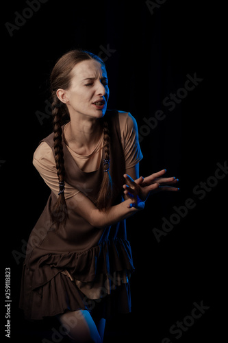Foto Girl Actress on stage plays emotions in blue theatrical light