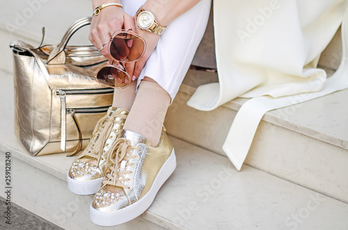 Obraz Golden sneakers, bag and watch closeup. Sunglasses closeup in female hands. The girl sits on the steps. - fototapety do salonu