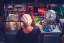 Asian Food, Street Food. Woman Prepares Food On A Mobile Cart