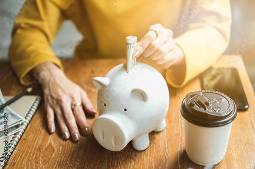 Foto  Asian woman saving money and dropping coin to piggy