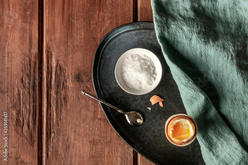 Fotografía  An overhead photo of a soft-boiled egg in an egg server with coarse sea salt and