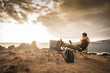 Travel and enjoying outdoor people concept with lonely man working on laptop internet connecetd computer sitting in front of an amazing sunset on the ocean - digital nomad millennial concept
