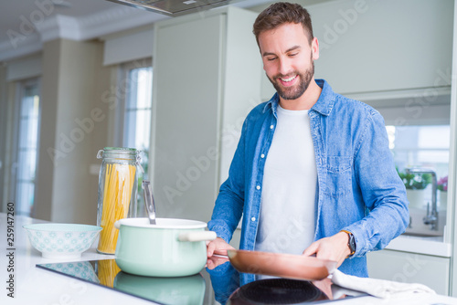 Fototapety, obrazy: Handsome man cooking pasta at home