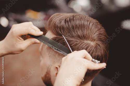 Close-up, master hairdresser does hairstyle with scissors comb Fototapete