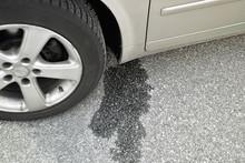 Spilled Engine Oil Or Gasoline Near The Car Wheels. Car Breakdown