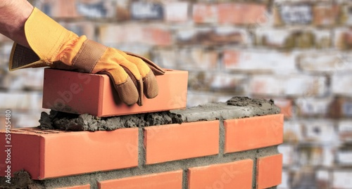Worker builds a brick wall in the - 259155480