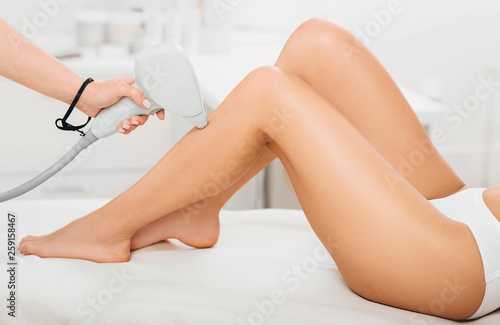 Foto beautician removes hair on beautiful female legs using a laser