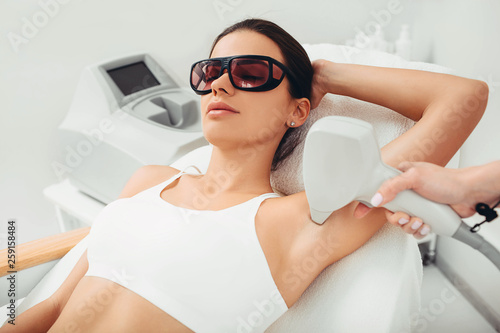 Beautiful woman having her armpit hair removed by female beautician Wallpaper Mural