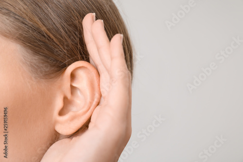 Stampa su Tela Young woman with hearing problem on light background, closeup