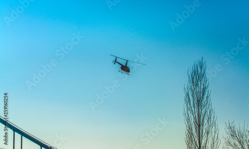 Staande foto Helicopter Silhouette of helicopter in blue clear sky with solar patches of light. Warm spring day. Modern transport.