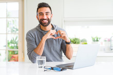 Handsome Hispanic Man Working Using Computer Laptop Smiling In Love Showing Heart Symbol And Shape With Hands. Romantic Concept.