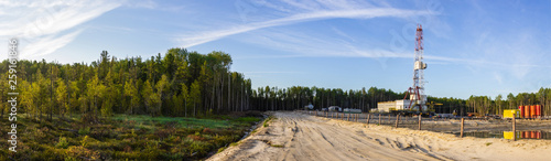 a panorama of a drilling rig on a sand dumping in the forest in the morning