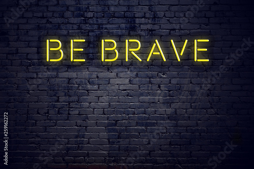 Photo  Night view of neon sign with text be brave
