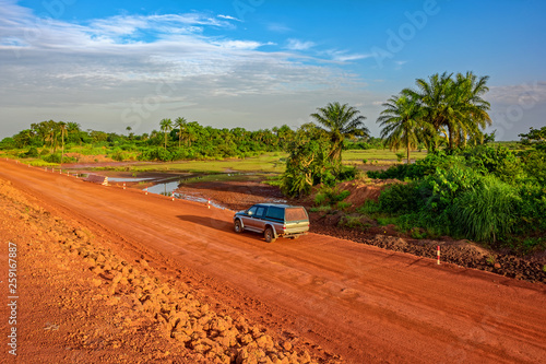 Sunset view of a typical red soils unpaved rough countryside road in Guinea, West Africa Wallpaper Mural