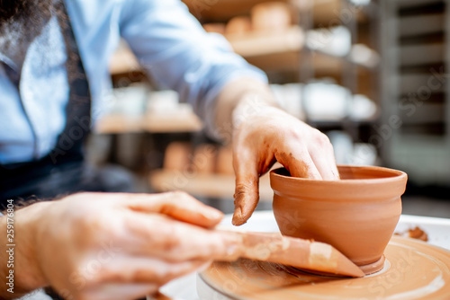 Man making clay jug forming shape by hands on the pottery wheel indoors, close-up view