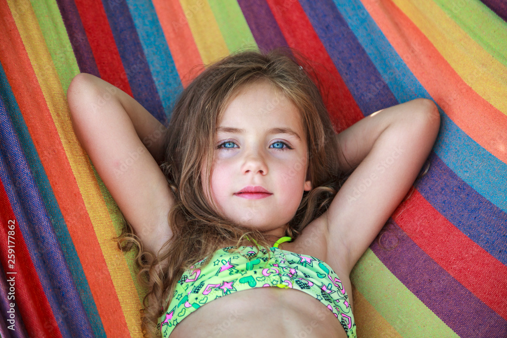 Fototapety, obrazy: Concept summer, vacation, weekend- beautiful blond-haired girl with blue eyes is lying on a bright hammock with rainbow colors