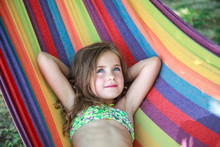 Concept Summer, Vacation, Weekend- Beautiful Blond-haired Girl With Blue Eyes Is Lying On A Bright Hammock With Rainbow Colors