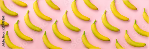 Geometric colorful fruit pattern. Bananas over pink background. Banner. Top view. Pop art design, creative summer concept. Minimal flat lay style.